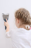 Little girl repairs wall Stock Image
