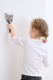 Little girl repairs wall Stock Photos