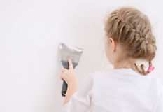 Little girl repairs wall Royalty Free Stock Photography