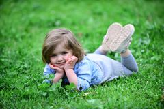 Little girl rest on grass. Little girl child rest on fresh spring grass stock photography
