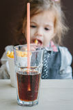 Little girl in a restaurant eating french fries and drinking cola. Stock Photo
