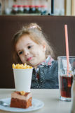 Little girl in a restaurant eating french fries and drinking cola. Stock Image