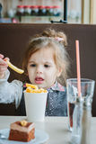 Little girl in a restaurant eating french fries and drinking cola. Royalty Free Stock Images