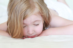 A little girl rested her head on her hands in bed Stock Image