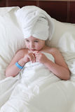 A little girl rested her head on her hands in bed Royalty Free Stock Image