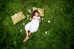 Little girl resting. On soft pillow in fresh spring grass Stock Image