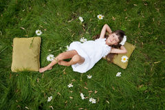 Little girl resting. On soft pillow in fresh spring grass Stock Photography