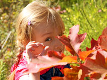 Little girl resting in autumn park Stock Photos