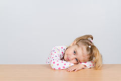 Little girl resting head on wooden surface at table. Royalty Free Stock Photography