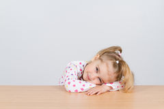 Little girl resting head on wooden surface at table. Royalty Free Stock Photo