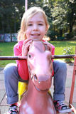 A little girl resting on a horse in park Royalty Free Stock Photography