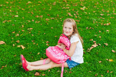 Little girl resting in a park after school Royalty Free Stock Photos
