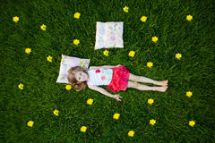 Little girl resting on pillows in summer garden Stock Photos
