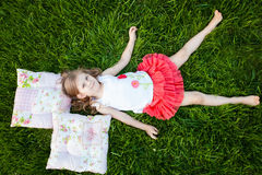 Little girl resting on pillows in summer garden Royalty Free Stock Image