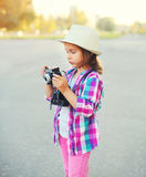 Little girl with retro camera doing snapshot outdoors Stock Photos