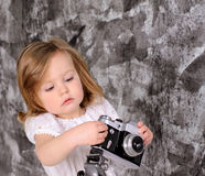 little girl with retro camera on rack indoors Stock Photo