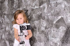 Little girl with retro camera on rack indoors stock photography