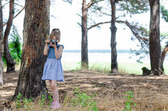 A little girl with a retro camera takes pictures in the forest, Stock Photos