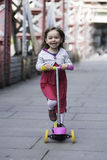 Little girl ridding scooter Stock Images