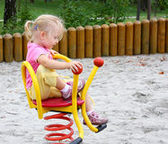 Little girl ridding spring swing Royalty Free Stock Photos