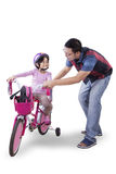 Little girl ride bicycle with dad in studio Royalty Free Stock Photo
