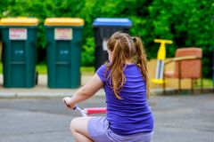 Little girl ride a pink bike from back in park. Riding bicycle on street stock photography