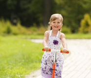 Little girl ride the scooter in the park. On green background Royalty Free Stock Photo