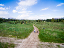 Little girl rides bicycle on country road Stock Photo