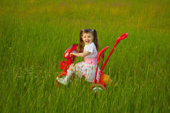 Little girl rides a bicycle on field Royalty Free Stock Photo