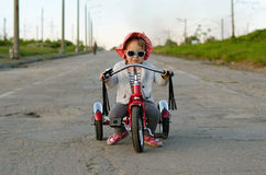 Little girl rides a bicycle Stock Photography