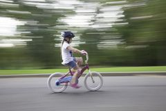 Little Girl Rides Bicycle Without Training Wheels. A little girl is just learning to ride her bicycle without training wheels.  She wears a helmet, and other Royalty Free Stock Photography