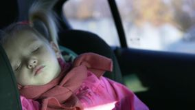 A little girl rides in a car in a car seat. Baby is sleeping. On the girl a pink jacket and a pink scarf stock video