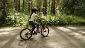 Little girl rides her bike on a forest trail