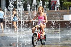 Little girl rides his bike among fountains Royalty Free Stock Photos