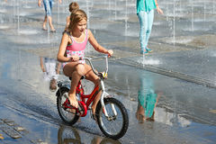 Little girl rides his bike among fountains Stock Images