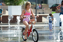 Little girl rides his bike among fountains Royalty Free Stock Images