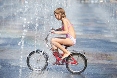 Little girl rides his bike among fountains Stock Photography