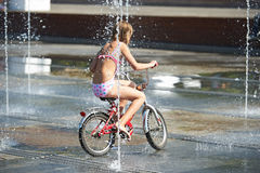Little girl rides his bike among fountains Stock Photo