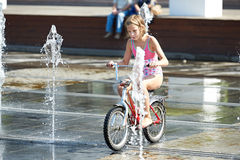 Little girl rides his bike among fountains Stock Image
