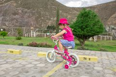 The little girl rides a pink bike in a hat. Summer walk. In the background - the landscape of mountains. Summer day stock photos