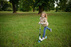 Little girl rides the scooter in park. Royalty Free Stock Images