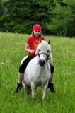Little girl riding. Beauty intent girl riding bareback by white ponny stock photos