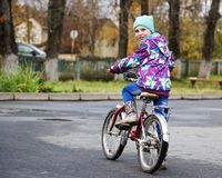 Little girl riding a bicycle in the autumn park Royalty Free Stock Photos