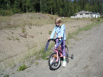 Little girl riding bike Stock Photos
