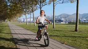 A little girl is riding a bike along the seafront alley, steadicam shot. stock video footage
