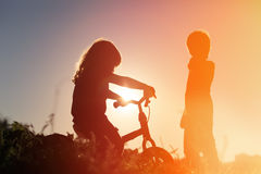 Little girl riding bike and boy at sunset sky Stock Image