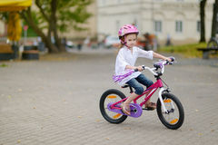 Little girl riding a bike in a city Stock Photos