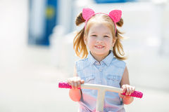 Little girl riding a bike in a city. Royalty Free Stock Images