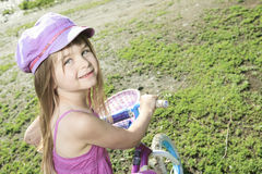 Little girl riding a bike on the country road Royalty Free Stock Image