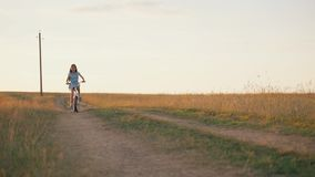 A little girl riding a bike on a country road. A girl rides a small bike across the field at sunset. stock video footage